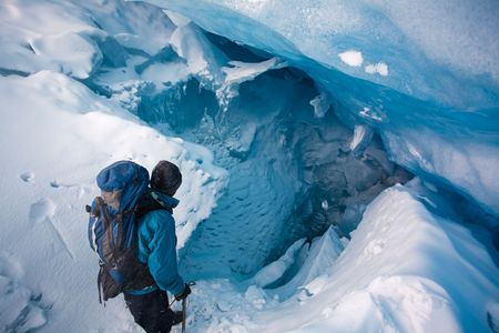 Young man explores ice cave at the toe of a glacier in the Rocky Mountains, Banff National Park, Alberta, Canada.