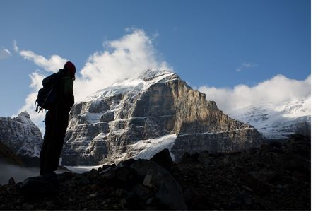 Silhouette of woman standing beneath high peak of the Rocky Mountains, Banff National Park, Alberta, Canada.