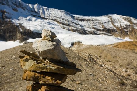 Rock cairn and glacier-capped mountain in the Canadian Rockies, Iceline, British Columbia, Canada.