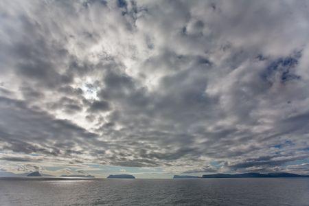 Dramtic clouds above the islands and ocean, Faroe Islands, Scandinavia