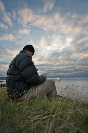 Young man reads a book by the ocean under dramatic skies, Faroe Islands, Scandinavia