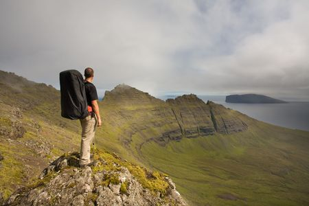 Young man backpacking among green mountains high above the ocean, Faroe Islands, Scandinavia