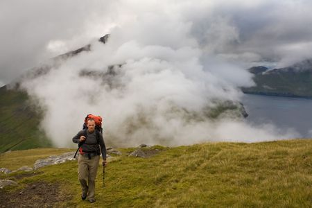 Young man walking among misty green mountains high above the ocean, Faroe Islands, ScandinaviaFaroe Islands, Scandinavia