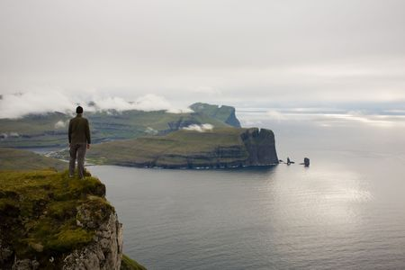 Young man stands at the edge of a cliff abve the ocean, Faroe Islands, Scandinavia Stock Photo