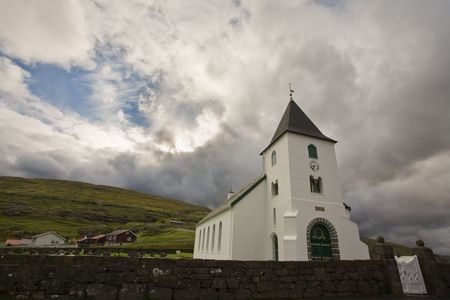 White church towers above small village, Faroe Islands, Scandinavia Stock Photo