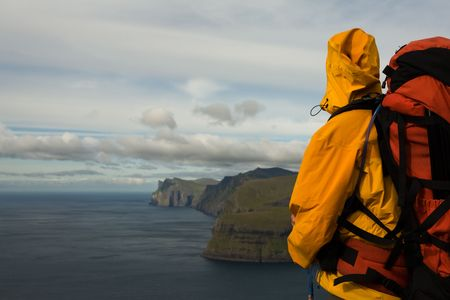 Young man swith backpack tands at the edge of a cliff abve the ocean, Faroe Islands, ScandinaviaFaroe Islands, Scandinavia