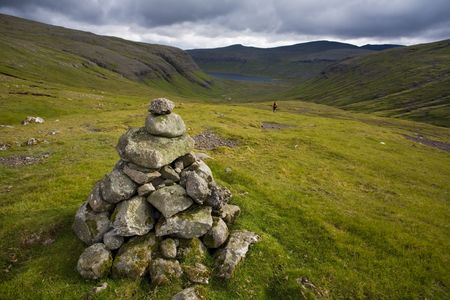 Hiker makes his way down a green valley, with cairn in the foreground, Faroe Islands, Scandinavia Stock Photo