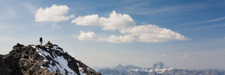 Climber reaches snowy summit in the Rocky Mountains, Kananaskis Country, Alberta, Canada.