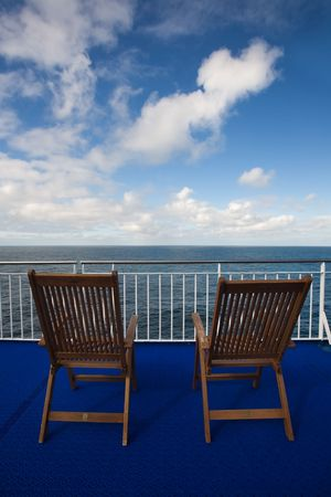 Two deck chairs on crusie ship with white clouds in the background, Norway, Scandinavia