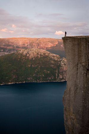unspoiled: Silueta de preson de pie al borde del inmenso acantilado, muy por encima del agua, Lyse, Noruega, Escandinavia Foto de archivo