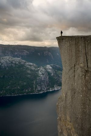 baratro: Silhouette di preson in piedi sul bordo del grande rupe, alta sopra l'acqua, Lysefjord, Norvegia, Scandinavia