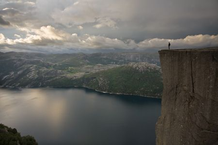 unspoiled: Silhouette of preson standing at the edge of immense cliff, high above the water, Lysefjord, Norway, Scandinavia