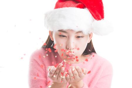 tatter: Mujer joven que sopla con sombrero de Navidad y un su�ter de color rosa aisladas en blanco.
