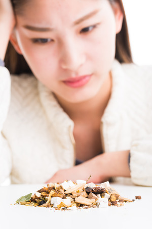 chinese herbs: woman looking at a pile of Chinese herbs. Stock Photo