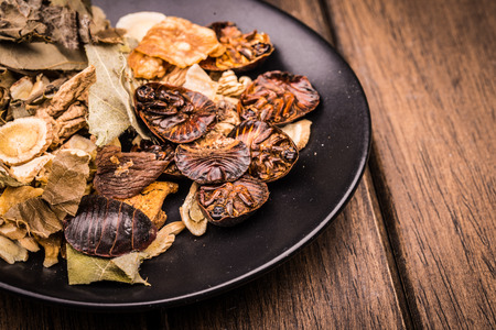 Close up view of Chinese traditional herbs in the black plate over board. photo
