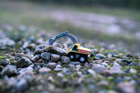Toy excavator on the rocky ground close up view