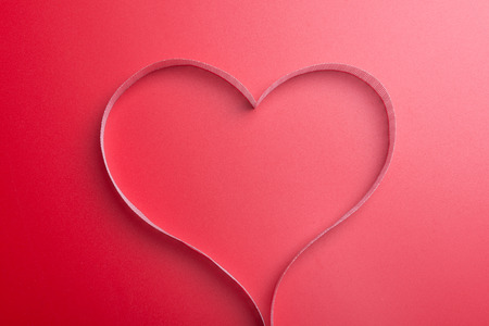heartshaped: Red ribbon on red background Stock Photo