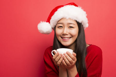 A young woman in a Christmas hat is drinking coffee Stock Photo
