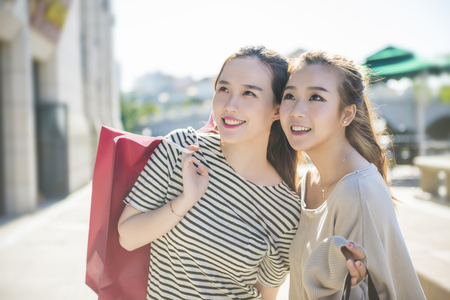 Young Asian female friends shopping together holding shopping bags Imagens