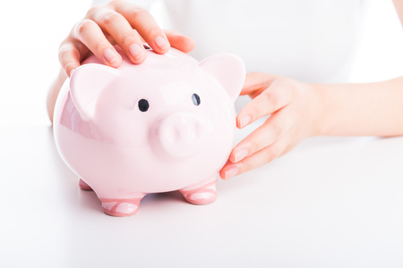 Hand holding a piggy bank on white background