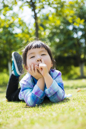 A cute little girl playing in the park lying on the grassland