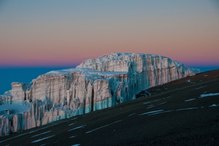 appear: The early morning sun beginning to appear on the glaciers on the crater rim of Kilimanjaro
