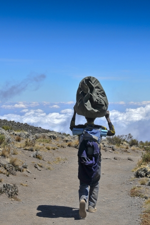 walking zone: A porter  walking above the clouds on Marangu route passing through the moorland zone on his descent from Kilimanjaro Stock Photo