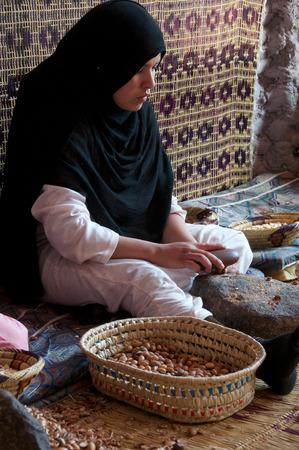 cooperativa: M�todo tradicional de producci�n de aceites de arg�n, una mujer bereber de trabajo con nueces de arg�n para extraer el n�cleo de una cooperativa de mujeres en Imlil en Marruecos Editorial