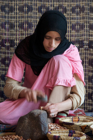producing: Traditional method of producing Argan oils, a Berber lady working with Argan nuts to extract the kernel in a womens cooperative in Imlil in Morocco