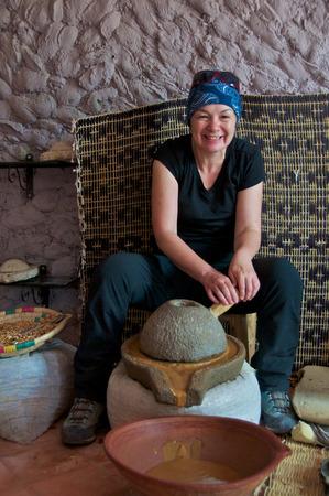 cooperativismo: Trekker Mujer moliendo granos de arg�n en una pasta en una cooperativa de mujeres en Imlil en Marruecos