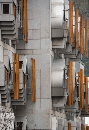 scottish parliament: The unique facade of the Members office accommodation quickly became the first iconic image of Holyrood. The windows are made from stainless steel and framed in oak, with the oak lattices providing privacy and shade Editorial