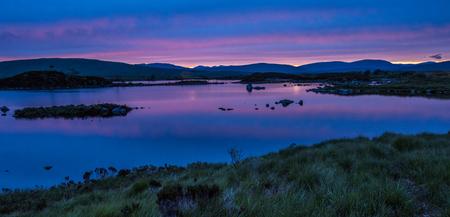 Reflecties van de late avondlucht op midzomer in de kleine lochan op Rannoch Moor, in de buurt van Glencoe in de Schotse Hooglanden Stockfoto
