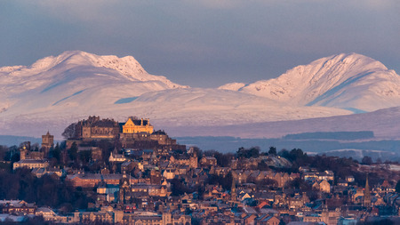 The early morning light on Stirling castle and wintery hills beyond