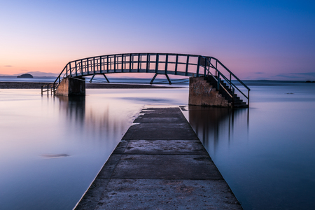 This bridge is known as The Bridge To Nowhere and was built as part of Dunbars Victorian beach improvement scheme. It crosses Biel Water where it flows in Belhaven Bay and the North Sea at Dunbar 스톡 콘텐츠