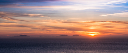 Looking out across the sea to the Western Isles off the coast of Scotland at sunset Stok Fotoğraf