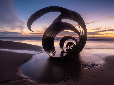 Sunset at the beach at Cleveleys on the Lancashire Coast with the artwork Mary's Shell  in the foreground Stock Photo