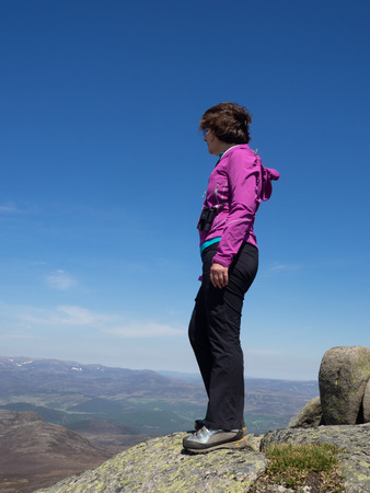 A mature lady looking out over the Scottish countryside from a view point high on the hills during a hike Imagens