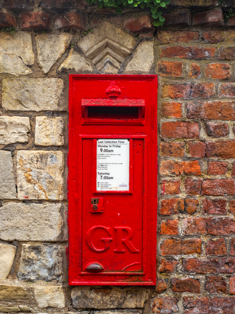 A red British post box made by A Handyside in Derby for the Royal Mail postal service in the UK