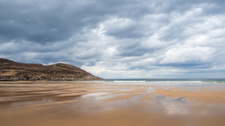 Torrisdale Bay is a fabulous mile-long beach, with clean golden sands, on the north coast of Sutherland, Scotland. An outstanding beach with superb dunes, Torrisdale Bay is reached from Invernaver. the beach is a popular place with surfers who enjoy the challenging tides. Stock Photo