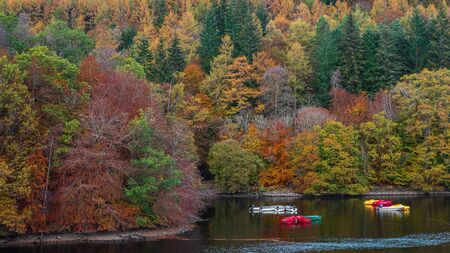 Autumn colours in the trees and small rowing boats on Loch Faskally at Pitlochry in highlands of Scotland