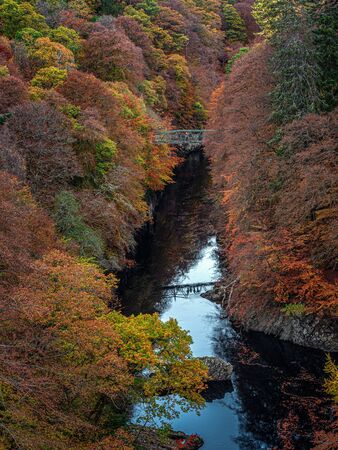 The footbridge over the River Garry gorge near Killiecrankie in the Scottish Highlands  in wonderful Autumn colours