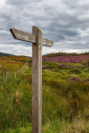 A wooden sign post covered pointing the direction to Inverssnaid and Aberfoyle in the Trossachs National Park