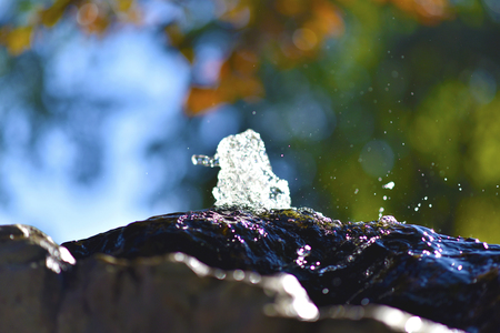 Water fountain in park, the water is flowing on a rock. Banco de Imagens