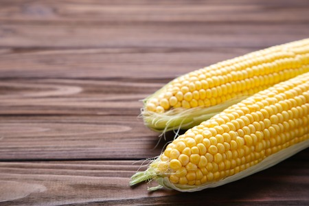 Fresh corn on cobs on a brown wooden table, closeup