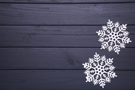 Snowflakes on a black wooden background. Christmas concept. Фото со стока