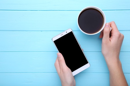 Female hands holding cup of coffee and smartphone on blue wooden background. Smartphone with black screen.