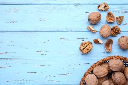 Walnuts kernels in basket on blue wooden background. Walnuts kernels on blue wooden table