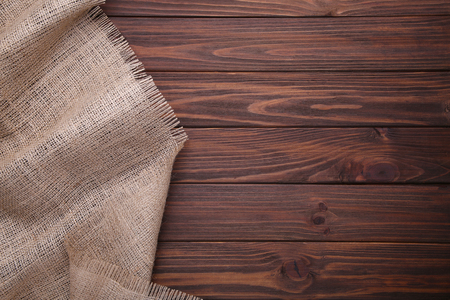 Natural sackcloth on brown wooden background. Canvas on brown wooden table 스톡 콘텐츠