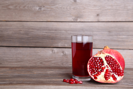 Ripe pomegranates and fruit juice glass on grey wooden background