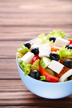 Fresh vegetable salad on brown background Imagens